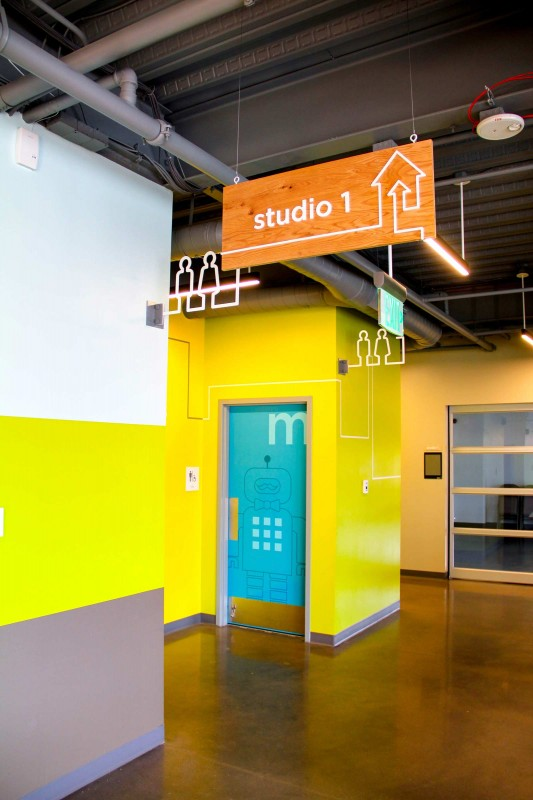 Hanging signage, routed metal blade signs and colorful robots incorporate an Etch-A-Sketch line motif to delineate bathrooms and wayfinding destinations at the Children's Museum of Denver at Marsico Campus. Credit: Zach Kotel, ArtHouse Design